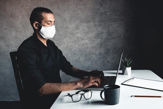 Un uomo mascherato lavora al computer. pandemia, coronavirus, epidemia