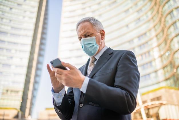 Uomo d'affari maturo mascherato che usa il suo smartphone all'aperto, covid e concetto di coronavirus