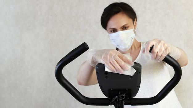 La donna mascherata pulisce il simulatore con un panno disinfettante per prevenire la diffusione del virus. fermare il coronavirus. covid19. posto per il testo. copia spazio