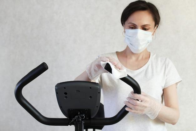 La donna mascherata pulisce il simulatore con un panno disinfettante per prevenire la diffusione del virus. fermare il coronavirus.