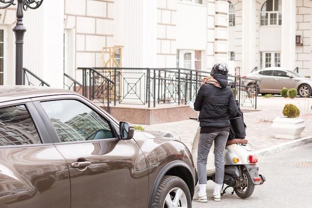 Donna mascherata che consegna cibo su una moto