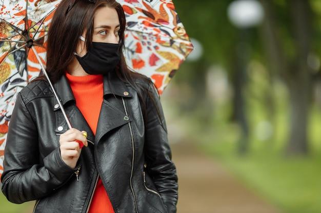 Una donna mascherata sta camminando lungo la strada. una donna in una maschera protettiva cammina nel parco con un ombrello sotto la pioggia. infezione da coronavirus covid-19