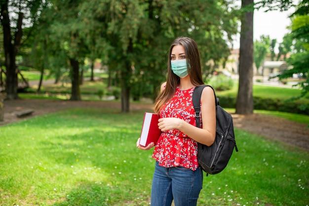 Studentessa mascherata che tiene un libro all'aperto