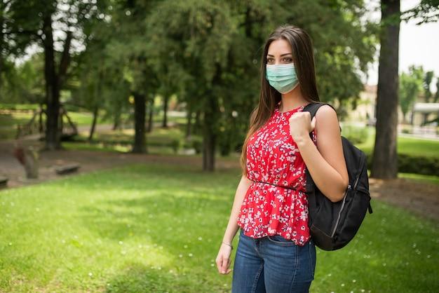 Studentessa mascherata che cammina in un parco, concetto educativo di coronavirus covid-19
