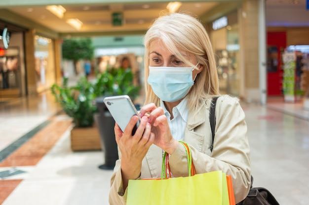 Donna mascherata che utilizza il suo cellulare mentre cammina in un centro commerciale