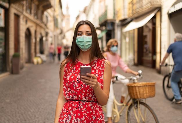 Donna mascherata che cammina in una città mentre si utilizza il suo telefono cellulare
