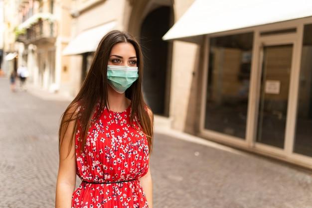 Donna mascherata che cammina in una città