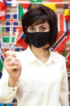 Donna mascherata con la siringa in mano, concetto di vaccinazione contro il coronavirus.