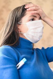 Giovane donna mascherata con mal di testa