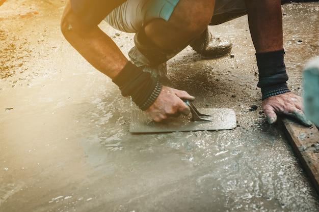 Muratore che costruisce un massetto in cemento a casa