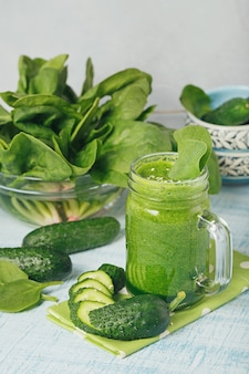Le tazze del barattolo di muratore hanno riempito di spinaci verdi freschi e di frullato di cetriolo su fondo di legno azzurro. cibo sano e concetto vegetariano.