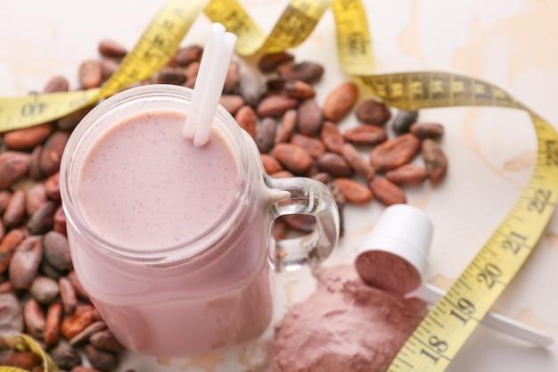 Barattolo di vetro di frullato proteico con fave di cacao su bianco
