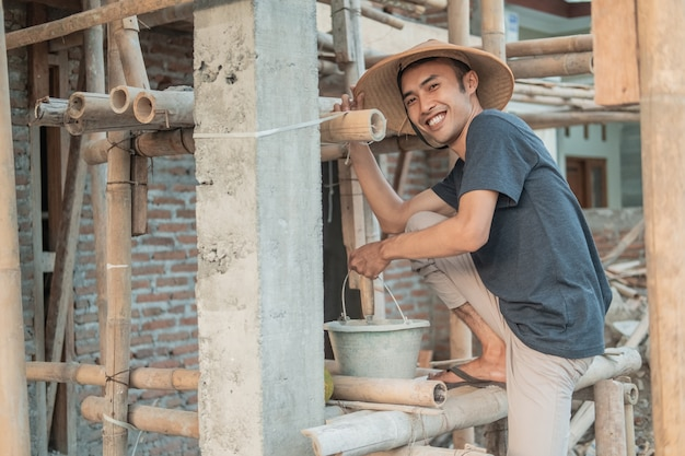 Mason sorride alla telecamera mentre trasporta secchi pieni di cemento e pasta di sabbia in una casa non finita