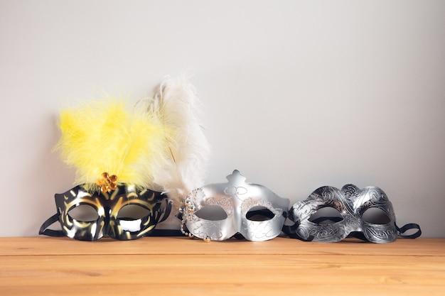 Maschere di travestimento sullo sfondo del tavolo in legno