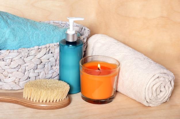 Spazzola da massaggio con manico in legno, crema per il corpo, candela profumata e cesto di vimini con asciugamani.