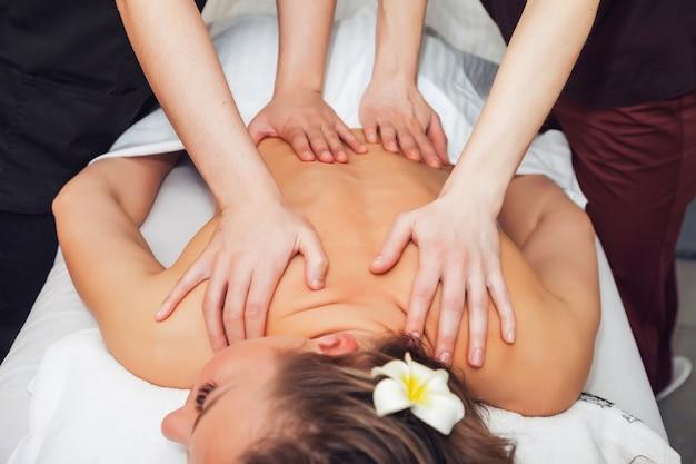 Massaggio a quattro mani nel salone spa. due massaggiatori fanno un massaggio alla schiena per la donna. massaggio tantrico sensuale a 4 mani di massaggiatore professionista. concetto di assistenza sanitaria e bellezza femminile