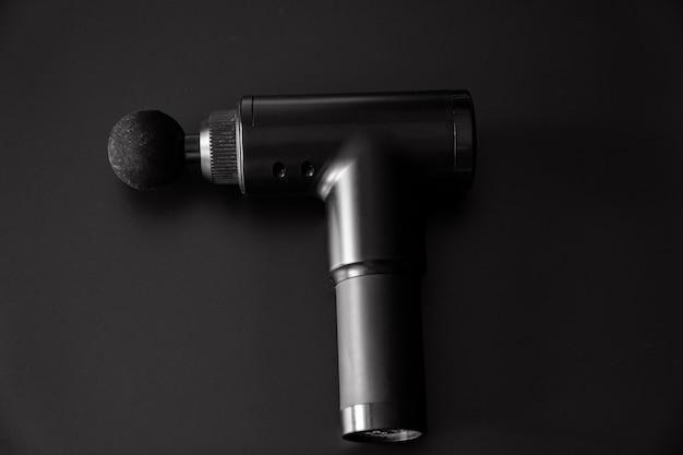 Pistola per massaggi su sfondo nero. dispositivo medico-sportivo aiuta a ridurre il dolore muscolare dopo l'allenamento, aiuta ad alleviare la fatica, colpisce le aree problematiche del corpo, migliora le condizioni della pelle.