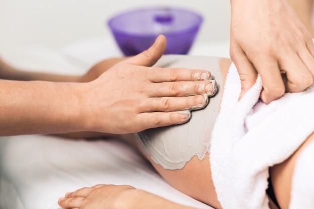 Massaggio delle gambe con argilla blu nella spa. clinica cosmetica, spa, centro benessere, concetto di assistenza sanitaria.