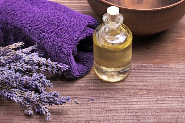 Bottiglia di olio da massaggio e fiori di lavanda su fondo in legno