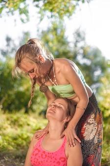 Il professionista del massaggio mostra metodi di massaggio rinfrescanti in una radura della foresta.