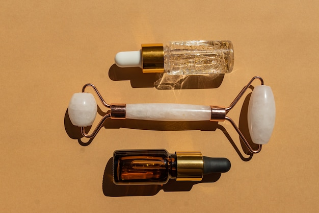 Rullo massaggiante per il viso in quarzo rosa con flacone di siero oro 24k e olio essenziale su fondo beige. il concetto di cura della pelle a casa.