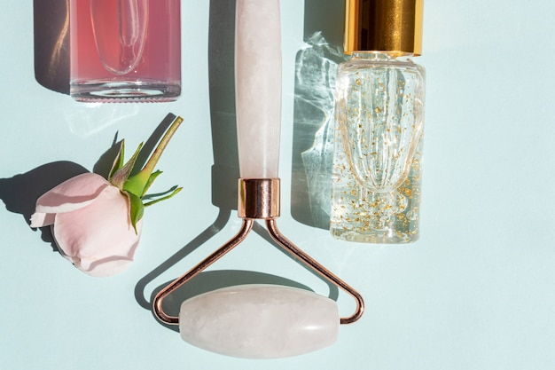 Rullo massaggiante per il viso in quarzo rosa con flaconi di olio cosmetico o siero su sfondo blu. il concetto di cura della pelle a casa. siero oro 24k e acqua di rose per il trattamento del viso.