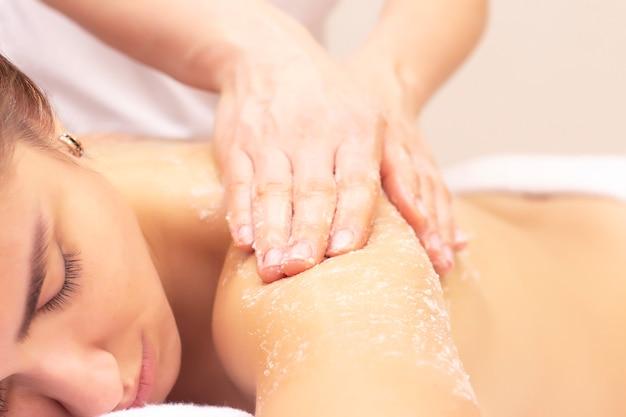 Massaggio e pulizia della pelle con uno scrub. bella ragazza ottiene una macchia in un salone spa.
