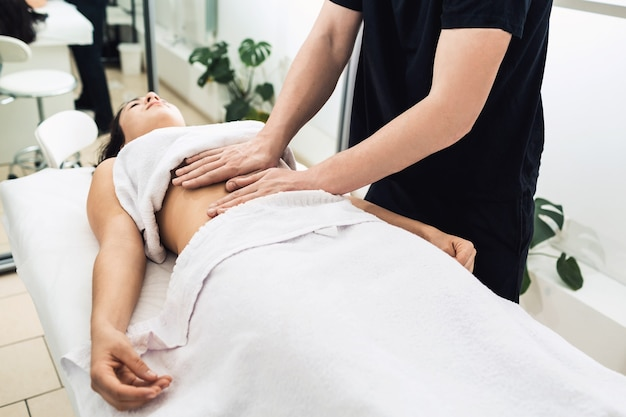 Massaggio dello stomaco nella spa. clinica cosmetica, spa, centro benessere, concetto di assistenza sanitaria.