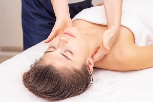 Massaggio e allungamento dei muscoli cervicali. bella ragazza ottiene massaggio in un salone spa. foto di toni chiari. reumatismi, artrosi