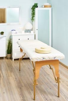 Lettino da massaggio, armadietto estetista, dettagli interni del salone di bellezza