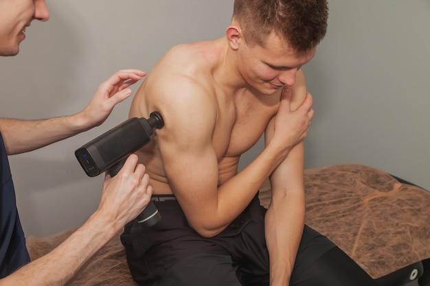 Il massaggiatore tratta la lesione del paziente maschio dell'atleta professionista. massaggi d'urto con pistola sportiva nell'ufficio medico della palestra. terapia a percussione per il massaggio rigenerativo del corpo atletico. fisioterapia