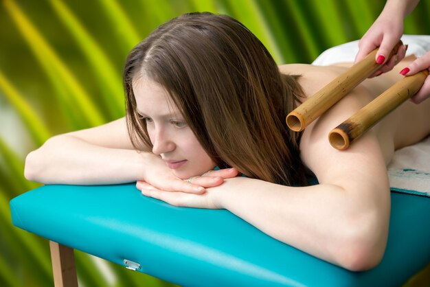 Massaggio con bastoncini di bambù per una giovane ragazza