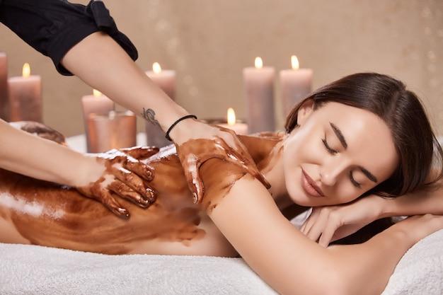 Massaggio con cioccolato nella spa sulla bella ragazza