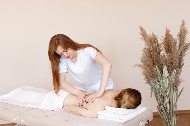 Il massaggiatore fa un massaggio alla schiena al cliente nel salone della spa