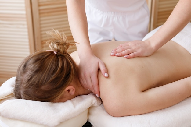 Il massaggiatore fa un massaggio alla schiena all'uomo