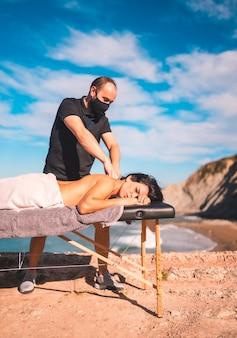 Massaggi sulla costa vicino al mare, massaggiatrice con maschera facciale nella pandemia di coronavirus