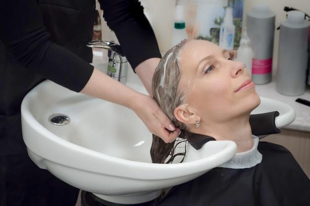 Massaggiare cute e capelli con shampoo. lavaggio dei capelli nel salone.
