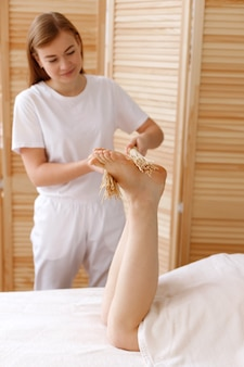 Il massaggiatore fa un massaggio ai piedi con le scope