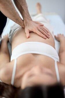Massaggiatore che fa massaggio alla pancia della donna incinta nel salone della stazione termale. concetto di trattamento di bellezza. fisioterapista che massaggia la donna gravida sdraiata sul divano in un armadietto leggero. concentrarsi su mani, braccia Foto Premium