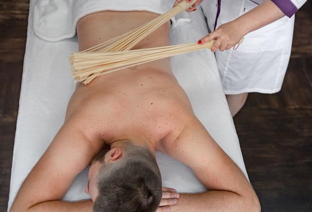 Il massaggiatore fa un massaggio giapponese a un uomo con scope di bambù.