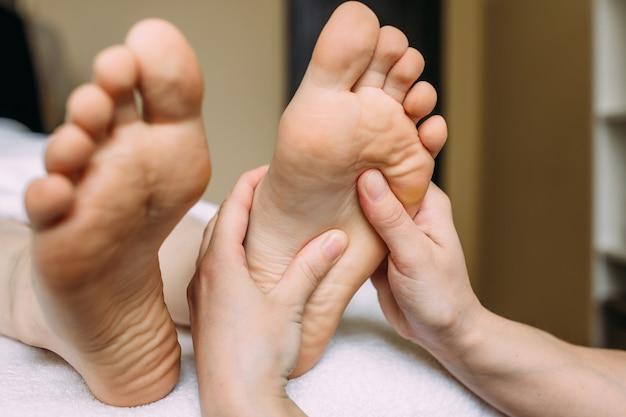 Il massaggiatore fa un massaggio ai piedi femminili alla spa
