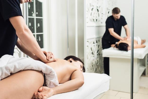 Uomo del massaggiatore che fa massaggio alla schiena.