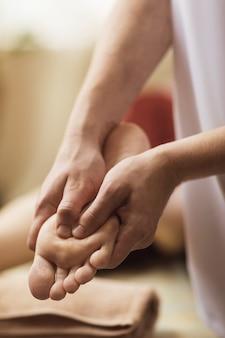 Il massaggiatore esegue una procedura di massaggio ai piedi, primo piano