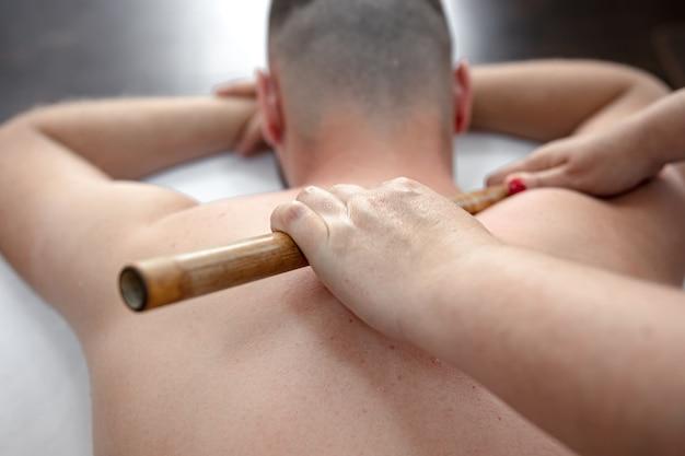 Il massaggiatore che utilizza bastoncini di bambù per massaggi durante il trattamento.