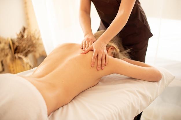 Massaggiatrice che fa massaggio alle spalle e alla schiena