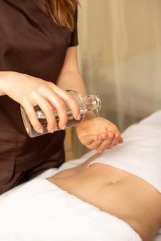 La massaggiatrice tiene una bottiglia trasparente di olio