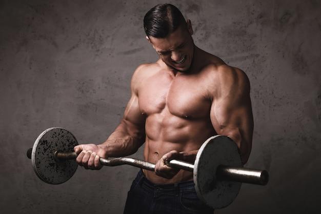 Enorme bodybuilder brutale che fa esercizi per bicipiti con il bilanciere