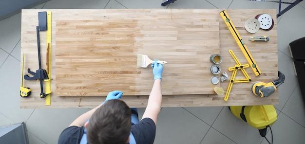 Il maestro applica il conservante per legno con il pennello sul posto di lavoro.