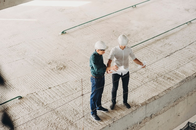 Maestro e architetto ispezionano la pianta dell'edificio mentre ispezionano come stanno andando i lavori.