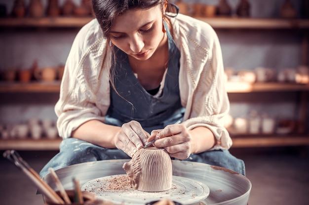 Il maestro ceramista crea una pentola di terracotta su un tornio da vasaio